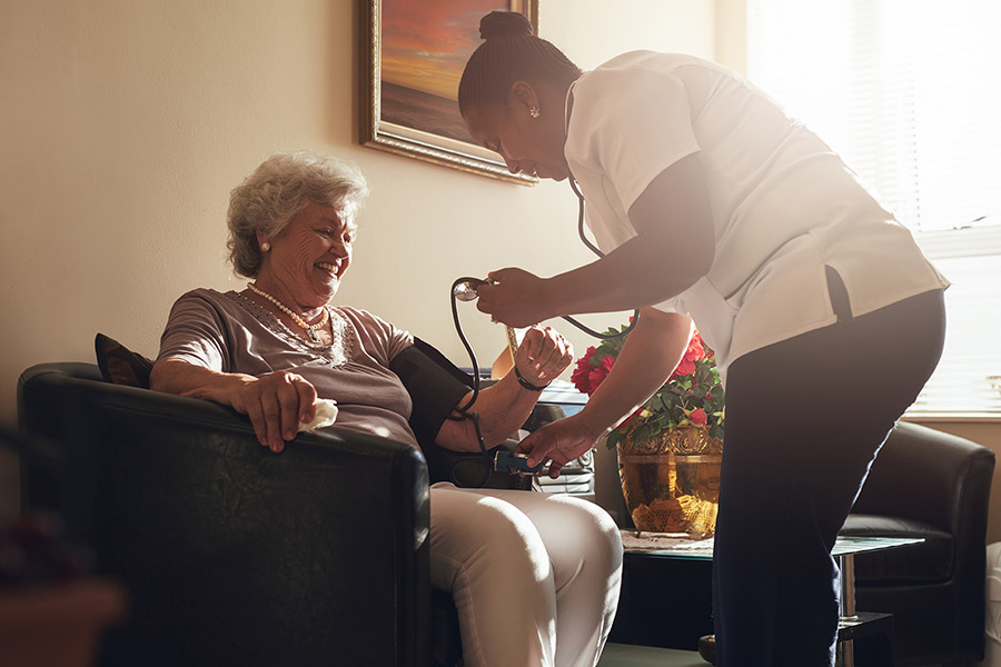 Nurse measuring blood pressure of senior woman patient in retirement home. Home caregiver doing routine checkup of a mature female patient.